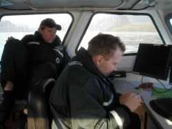 Lieutenant Commander Mark Wetzler, operations officer on the FAIRWEATHER, fighting a losing battle with the mouse. Photo