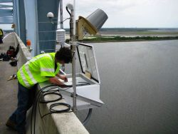An employee of NOAA's Center for Operational Oceanographic Products (CO-OPS) installs an air gap sensor on the Don Holt Bridge Photo