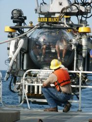 Deck-hand on the R/V SEWARD JOHNSON crouching in front of the Johnson Sea-Link II submersible as it is launched from the ship. Photo