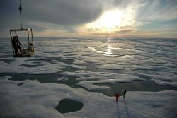 The science team descends onto the ice below in a manlift. Photo