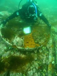A marine archaeologist taking measurements of the boiler face of the HASSLER. Photo