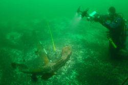 Dave McMahan, Alaska State Archaeologist, shooting video of large Kad'yak anchor. Photo