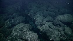A rugged area of pillow lavas and a large fissure in the seafloor. Image