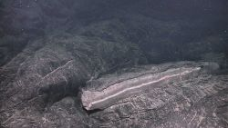 An oddly broken lava slab showing cooling zones of lava and pink and white alteration. Image