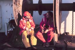 Two crewmen taking a breather during transit between fisheries studies stations. Photo