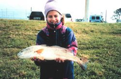 A smiling eight-year old displays the red drum that she caught at the Florida Power Plant discharge. Photo