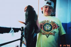 A young fisherman proudly displays a fish almost as large as himself Image