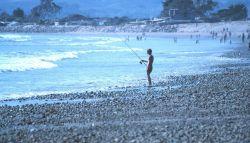 Angler surf fishing on beach. Image