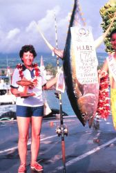 Angler standing next to 170 pound Yellowfin tuna caught during Hawaiian International Billfish Tournament. Photo