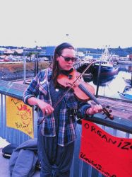 A violinist plays at the community fish fry in support of the United Seiners Association Photo