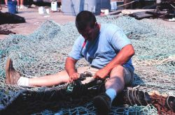 Mending fish nets at the Co-op Seafood dock Photo