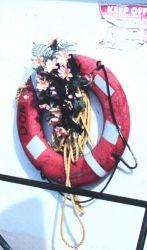 A decoration? A memorial? Perhaps a celebration? Flowers grace a shrimp boat in Conn Brown Harbor. Image