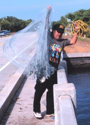 Photo -5a - A fisherman retrieving his net after casting for mullet and other fish off a bridge south of Everglades City. Photo