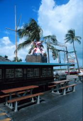 A giant rat advertising a Florida Keys fast food restaurant and seafood bar with giant plastic fish hanging in the background Image