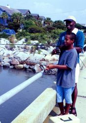 A man and his son visiting from Ohio try their luck at bridge fishing near Charleston, South Carolina Image