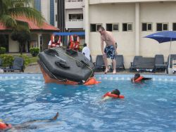 NOAA trainer John LaFargue instructing the Ghanaian observers on how to right the life raft Photo