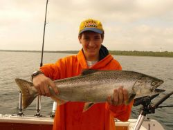 Young sport fisherman holding Atlantic salmon Photo