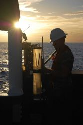 Scientist working with coring tubes at sunset. Photo