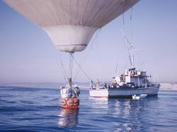 The YAQUI QUEEN, off La Jolla, either rescuing a downed hot air balloon or engaged in a bizarre attempt to use a balloon for observation purposes. Photo