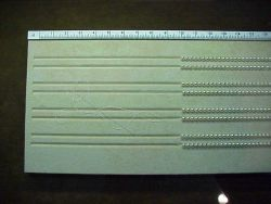 The slotted board used for stringing cultured pearls and measuring the length of the necklace or bracelet. Photo
