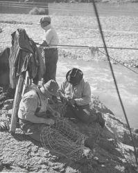 Indian fishermen repairing their nets Photo