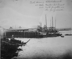 Fish curing establishments, fish freighter in the foreground. Photo