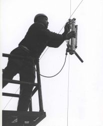 Deploying a Nansen bottle, used for measuring sub-surface temperature and to collect water samples for analysis. Photo