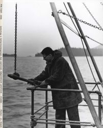 Lowering a bathythermograph in order to obtain the temperature profile of waters to 450 feet depth. Photo