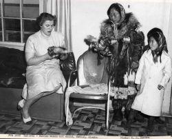 Eskimo woman and children selling fur dolls Photo