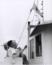 Raising the official flag of the Department of the Interior during dedication ceremonies on the ALBATROSS IV Photo