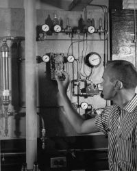James Delaney, fishery biologist, setting control device for delivery of sea water at preset temperature and salinity levels Photo