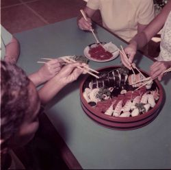 Diners trying to use chopsticks at sushi bar Photo