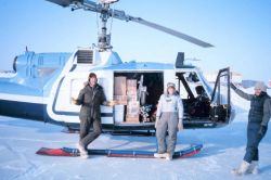 Brendan Kelley and Lori Quackenbush of the University of Alaska Fairbanks and NOAA helicopter mechanic Russ Talley (on right) loading Bell UH-1M with  Photo