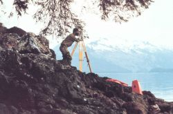Lieutenant (j.g.) Grady Tuell observing horizontal angles with Wild T-2 theodolite near the village of Hoonah. Photo