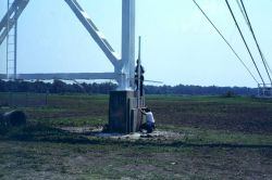 Rod man and level rod on overhead cable support anchor. Photo