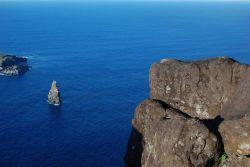 Human petroglyphs at Rano Kau overlooking the spire-like rock inshore of Moto Nui. Photo