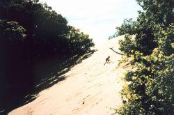 Boy climbing a large dune Photo