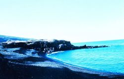 An arcuate cobble beach with a small volcanic rock outcrop at the end of the beach. Photo