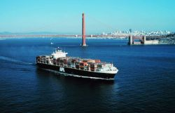 An outward bound containership with the Golden Gate and San Francisco skyline in the background. Photo
