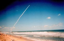 A space shuttle launch from Cape Canaveral provides a dramatic site for beach-goers. Photo