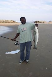 A lucky fisherman with a striped bass at Cape Henry. Photo