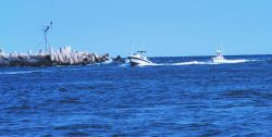 Recreational fishing boats passing the jetties at Manasquan Inlet Photo