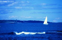 Newcastle light with sailboat on the port tack. Photo