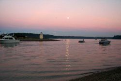 Moonrise over Gig Harbor as salmon fishermen try their luck in the shallows off the spit Photo