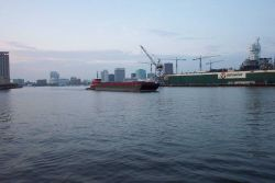 Tug pushing barge down the Elizabeth River with Norfolk skyline and shipyard in picture. Photo