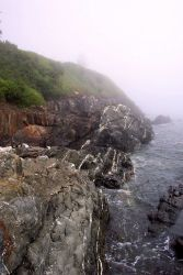 Quartz-veined metamorphic rocks meet the sea below a fog-shrouded lighthouse at West Quoddy Head. Photo