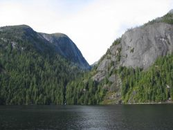 Ocean and evergreens in a scene reminiscent of Yosemite Valley. Photo