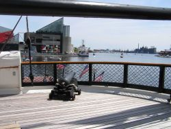 A cannon on the stern of the USS CONSTELLATION pointed at the stern of the NOAA Ship THOMAS JEFFERSON in the Inner Harbor. Photo