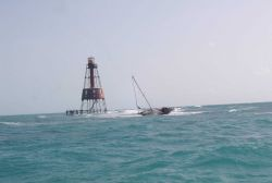 Carysfort Reef Lighthouse with derelict sailboat Photo