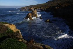 A gentle swell breaking against the rocks of the Granite Canyon area on the Big Sur coastline. Photo